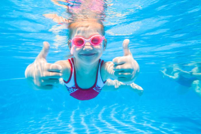 Meisje zwemt onder water en steekt duimen omhoog